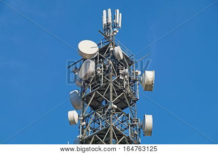 Telecommunication pole tower television antennas with blue sky background