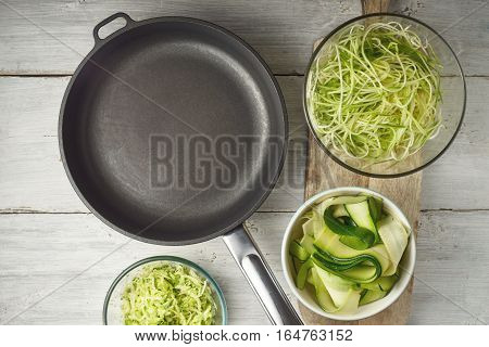 Raw zucchini noodles with pan on the white wooden table