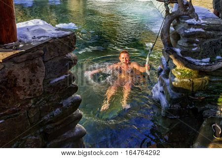 Lumshory Ukraine - January 10 2017: A woman dips into the icy mountain creek after bathing in the cast iron vat with mineral water containing hydrogen sulphide.