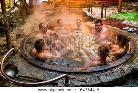 Lumshory Ukraine - January 10 2017: Tourists bathing in the cast iron vat with mineral water containing hydrogen sulphide. Water in cast iron vats heated to 40-45 degrees Celsius.