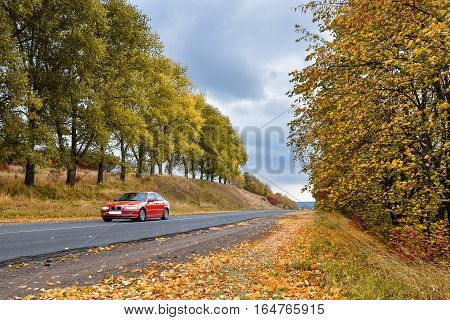 Empty asphalt road through the  autumn woods and blurry red car. Autumn scene with road in forest. Beautiful scenic empty road in the fall and woods. Asphalt road and old red car among the autumn forest