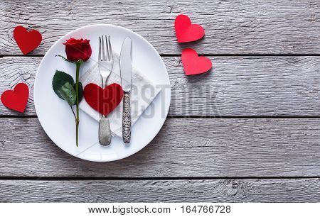Romantic dinner concept. Valentine day or proposal background. Top view of restaurant wooden table with heart and rose with cutlery on plate. Copy space on rustic wood