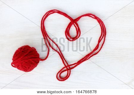 heart symbol of red thread on a light wooden surface top view / untied love affection