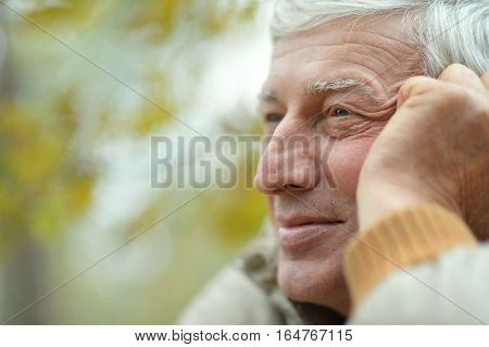 Portrait of thoughtful elderly man in autumn