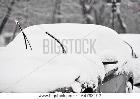 Windshield wipers of an snow covered car after heavy snowfall