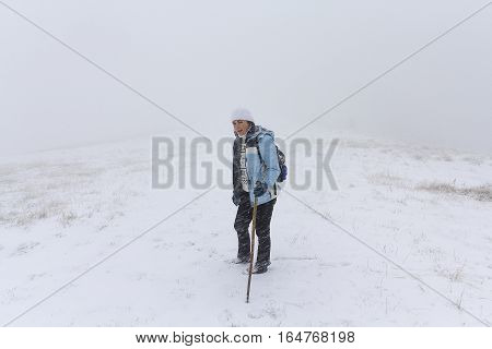 Girl - a tourist on the trail in the snow storm. People