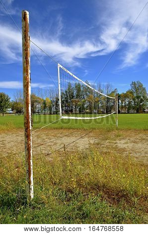A net reaches across a sandy and weedy outdoor volleyball court