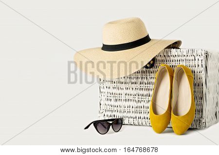 White wicker suitcase, women's hat sunglasses and yellow shoes.