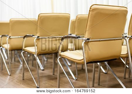 Rows of metal chairs at the conference in an empty room. Back view.