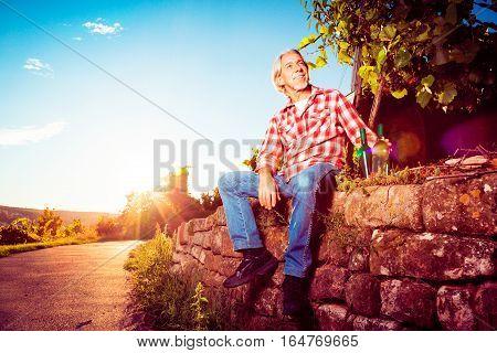 Senior winemaker standing by his vineyard, looking forward to the harvest.