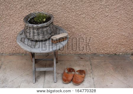 Vintage things:old French garden wooden folding table, wicker basket with flowers, old bright brown leather slippers, shoe brush with stiff bristles, background - yellow pink walls. Provence. France.