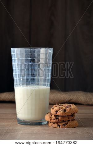 A glass of milk and cookies with chocolate chips on a dark background.