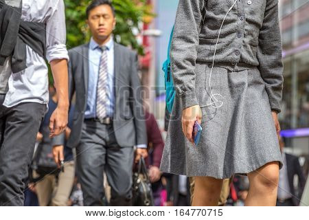 Hong Kong, China - December 6, 2016: asian business people in elegant uniform with mobile phone down the street market Jardine's Crescent, Causaway Bay, on the road full of shops