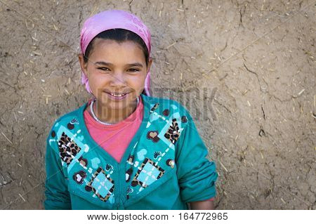 Errachidia Morocco - April 12 2016: Young Berber girl poses in front of her home in a small Berber village in the Ziz Valley near Errachidia Morocco.
