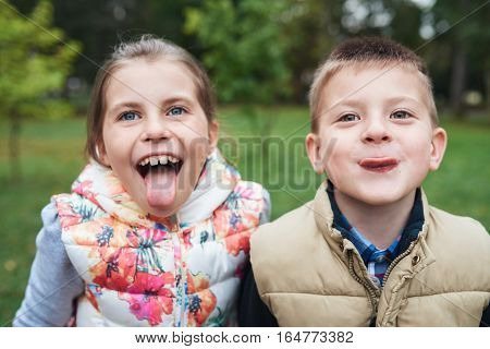 Portrait of a little brother and sister sticking out their tongues and making faces while enjoying a day outside together in autumn