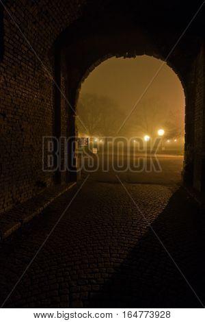 Old cobblestone path through gate inside Kalemegdan park at night covered in fog, Belgrade, Serbia