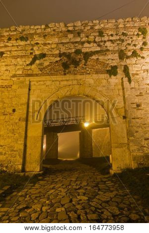 Old cobblestone path to Kalemegdan fortress at night covered in fog, Belgrade, Serbia