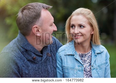 Smiling mature couple looking at each other while sitting together on a bench in a park in the autumn