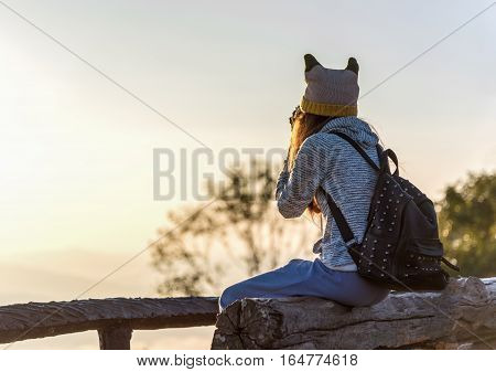 Woman sitting on the log and taking photos on the mountain.