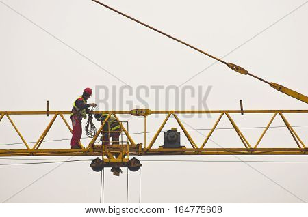 Workers inspecting and servicing a big construction crane in Belgrade, Serbia