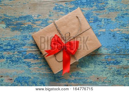 Gift box with a red bow on wooden background with crackling effect