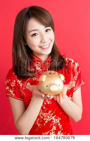beauty woman wear cheongsam and show gold piggy bank to you in chinese new year