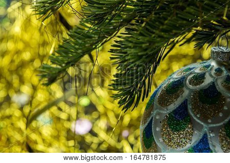 Glass sphere on a fur-tree paw and a light background