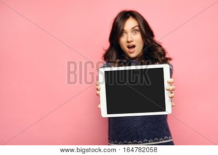 Shallow DOF. Focus on computer. blank tablet screen displayed to the viewer for text or advertisement. Shocked girl showing empty black display. Offer or sale concept