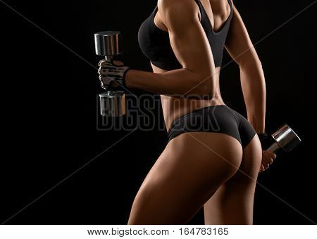 Backside to die for. Cropped closeup of perfectly shaped female buttocks of a fit and toned sportswoman with dumbbells in her hands