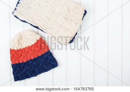 Colorful woolly hat and scarf on the white wooden background.