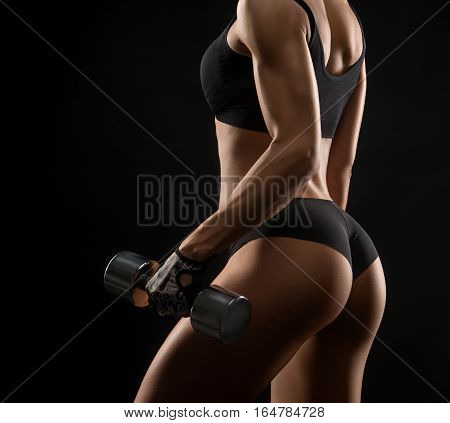 Pump your way to fitness. Cropped rearview shot of a fit woman in exercise clothing lifting weights against black background