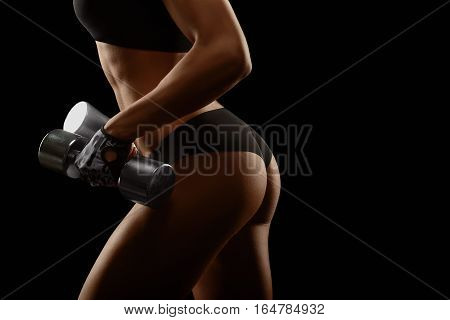 Better than yesterday. Cropped closeup of a fitness woman with sexy toned buttocks holding weights while exercising on black background copyspace