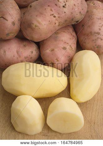 Peeled and unpeeled potatoes on wood desk closeup