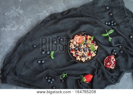 Healthy breakfast with muesli and berries on stone background. Flat lay top view