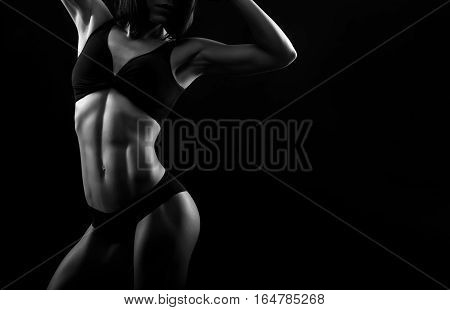 Every muscle is seen. Cropped monochrome studio shot of a stunning fit female wearing sports top and pants stretching her back showing off her perfect body copyspace