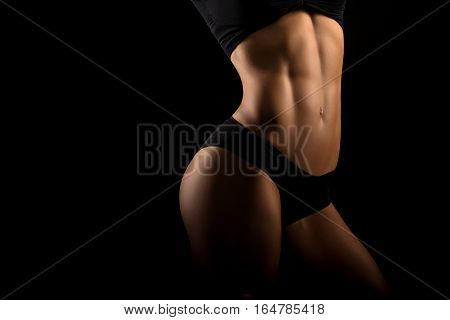 Fit girls are the best. Horizontal shot of a fitness woman in sportswear showing off her perfectly shaped toned strong body on black background copyspace