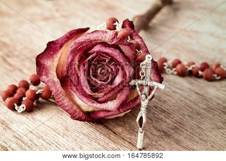 Silver crucifix and dry rose on wooden background