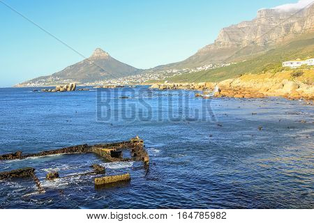 The Antipolis, a Greek oil tanker, ran aground on the rocks near Victoria Road in Oudekraal in the Cape Town, South Africa. Today there are only a few remains. Sentinel Peak on background.