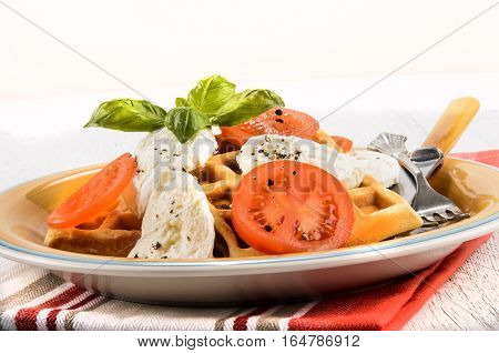 mediterranean salad with fresh tomatoes goat cheese with crushed peppercorn basil and waffle on a plate
