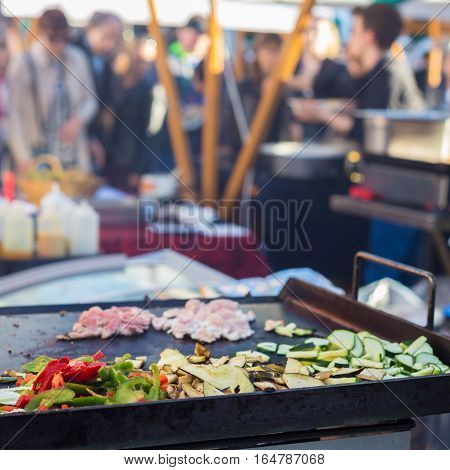 Chef making chicken with grilled vegetable tortilla wrap outdoor on street stall on Open kitchen international food festival event. Street food ready to serve on a food stall.