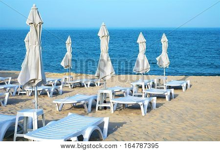 Empty sun loungers and closed umbrellas on a deserted sea sandy beach on a clear day.