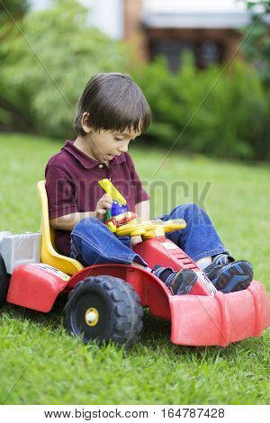 Happy Little Boy Driving A Toy Car