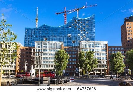 HAMBURG GERMANY - JUNE 25 2014: City of Warehouses district (Speicherstadt) in Hamburg Germany. Building of Elbphilharmonie (Elbe Philharmonic Hall) on the background