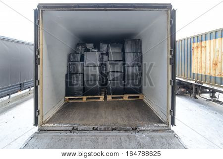 Road freight trailer loaded with boxes. Boxes wrapped in a black stretch film. Interior view of empty semi truck lorry