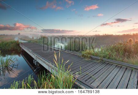 wooden biking bridge over river at sunrise in Holland
