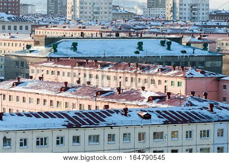 Snow-covered roofs of multi-storey town houses. View from above.