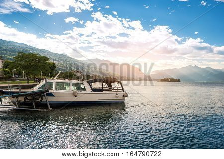 Boat on mountains background. Water and sky at daytime. Travel and admire true beauty.