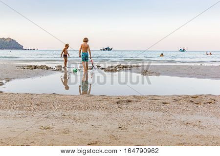 Ao Thong Nai Pan Yai, Koh Pangan, Thailand, April 22, 2016 - Two little boys play on a white sandy beach. Outside the shore there are some boats.