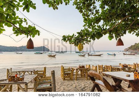 Tables and chairs on the beautiful beach Ao Thong Nai Pan Yai, Koh Pangan, Thailand. In the trees hang some lanterns.