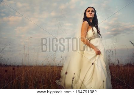 Bride looks far away while she stands on the field